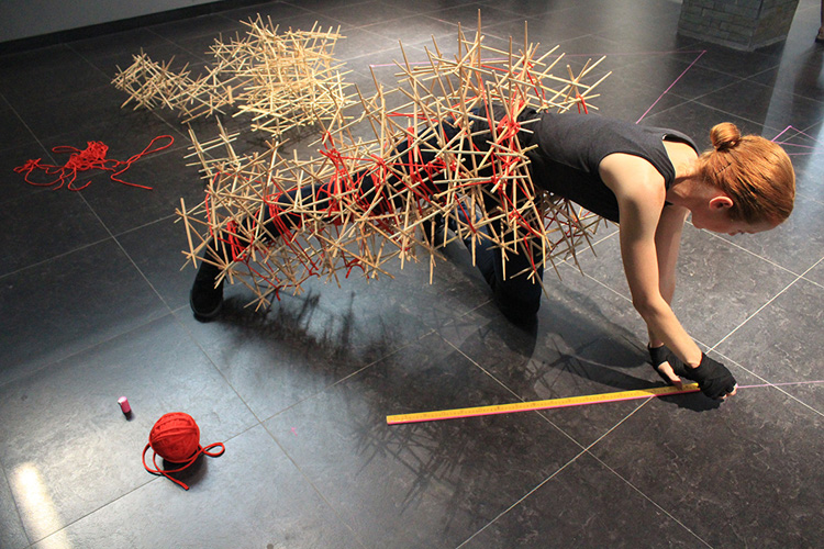 Untitled (action_structure_drawing), performance still, 2008, re-performed 2013, performance with bamboo structures, cotton twine, liquid-chalk floor-drawing, XLY Museum of Modern Art, Chengdu, China, 7 June 2013. Performer: Melanie Irwin. Photo: Ling Cheng